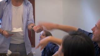 A young man loses control of a meeting while his coworkers throw paper at him. He yells at them in frustration while waving papers in the air in a dull office.