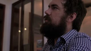 A young man with a full beard orders a beer and cools himself off with it and then takes of drink while talking to the bartender.