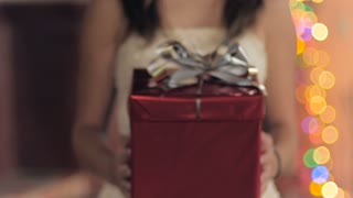 A young woman presents a red wrapped gift box with a silver bow towards the camera