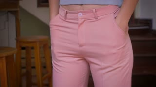 A young woman wearing pink pants pulls her hands out of her pockets to reveal that she has nothing in her pockets. No money, no keys, no cell phone, hand held shot.