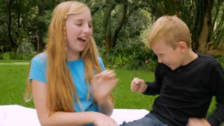 A younger brother and older sister tickle each other outside and smile at the camera - slowmo