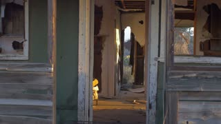 Abandoned old dilapidated house with broken window and old ruined furniture with open door, pealing paint, abandoned belongings, and sunlight streaming through broken wall.
