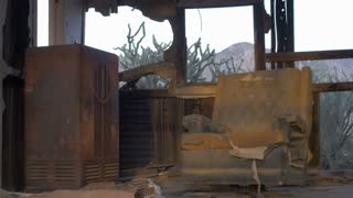 Abandoned old dilapidated house with old ruined fabric chair and standing antique radio, pealing paint, abandoned belongings, and sunlight streaming through broken wall with mountains and sky seen through the broken window.