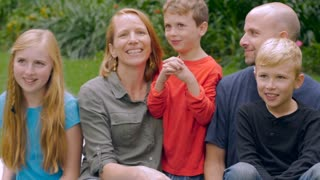 An adorable family of five smile and listen to their youngest child talk while having a picnic outside in a park.