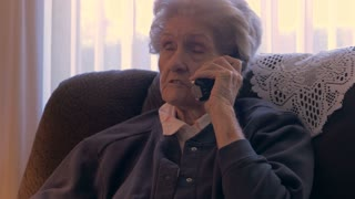 An aging, healthy, independent, senior in her 90s talks and laughs on a phone in her home in 4k dolly
