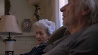 An aging mother and son visiting, laughing, and talking on a sofa side profile in 4k