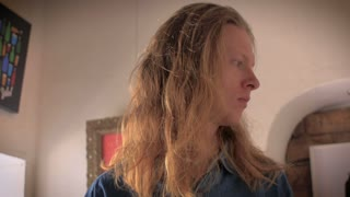 An attracting young blond man in his 20's pulls up and twists his long hair into a man bun.