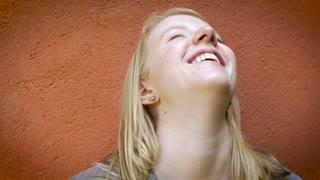 An attractive blond caucasian young millennial 20 something woman smiles, talks and laughs at the camera against an orange wall background.