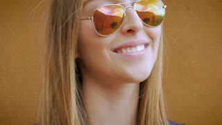 An attractive blond teenage girl smiles and takes off her sunglasses - hand held