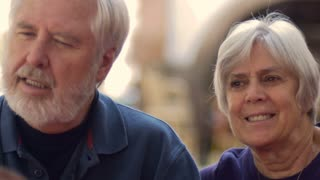 An attractive elderly couple with gray hair smiling and laughing outside. The baby boomer man has a gray beard and the senior woman has short hair both wearing blue.