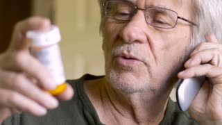 An attractive elderly senior calls in his medicine prescription to a pharmacy or doctors office on a flip phone in 4k.