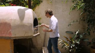 An attractive middle aged man bakes bread in a wood fired oven in slow motion