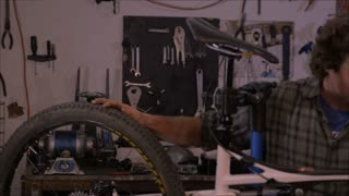 An attractive millennial man stands next to a bicycle in his workshop and smiles after he completes the work on the bike - Room for text