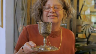 An attractive older jewish woman explains the significance of the kiddush cup at a passover seder