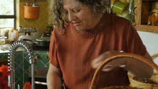 An attractive older, well dressed woman washing farm fresh eggs from a wicker basket in her kitchen sink