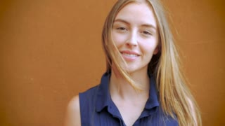An attractive teen girl with long blond hair smiles at the camera while her hair gently blows in the wind in slowmo
