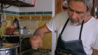 An elder man with an apron walks towards a middle aged man in slow mo in a kitchen with food on his hands.