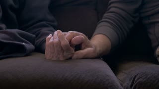 An elderly man holds his older mother's hand on a sofa dolly shot in 4k