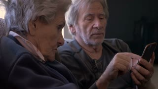 An elderly man shows a smart phone to an 90 year old woman who has trouble seeing it