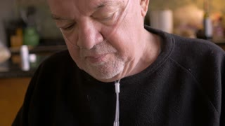 An elderly man wearing an oxygen therapy tube takes his medication from a daily pill planner in slow motion