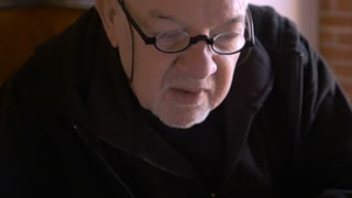 An elderly man wearing glasses gets computer lessons from another man while he asks questions and is about to take notes with a pen