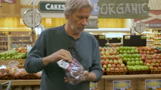 An elderly senior man picks out grapes while shopping in a modern generic supermarket with signs of organic produce in the background