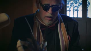 An elderly senior man wearing sunglasses and a colorful scarf performs a jazz song on a piano in creepy lighting with medium dolly tracking shot.