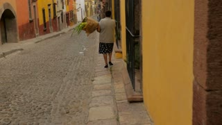 An elderly woman carries a bouquet of flowers down a colonial street in an old historic town - steadicam slow motion shot
