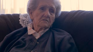 An elderly woman in her 90s, sitting on a sofa, talking and using her hands for emphasis in 4k