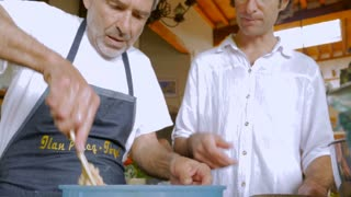 An eldery man instructs a middle aged man how to mix a bowl of food in a kitchen - low angle