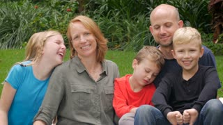 An entire family of 5 give the camera thumbs up and smile outside during the day in a park.