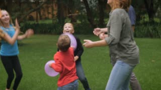 An entire family of five play together outside jumping and laughing - slowmo steadicam