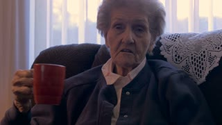 An old lady in her 90s telling a story and drinking a cup of coffee - dolly shot in 4k
