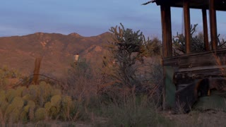 An old water tank, cacti, and abandoned house are seen during sunrise / sunset in the desert with a dolly shot.