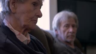 An old woman and man, or aging mother and son sit next to each other laughing and talking in 4k