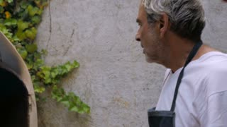 An older father and son look at the progress inside a wood fired oven while baking bread or matza in slow motion