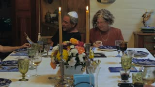 An older man reads from the haggadah at a passover seder and a woman has a small dog in her lap - dolly shot