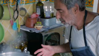 An older senior and middle aged man work together cooking in a home kitchen as a family - hand held