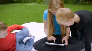 An older sister shows her two younger brothers something on a tablet outside in a park or garden - handheld slowmo