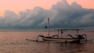 An outrigger fishing boat in Sanur Bali, Indonesia, calmly floats on the ocean during sunrise with large fluffy clouds and a spectacular sunrise in the background.