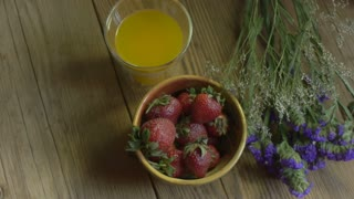 An overhead dolly shot of vine ripe strawberries and fresh squeezed orange juice displayed with purple flowers on a rustic wooden table.