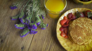 An overhead shot of a gourmet healthy breakfast of vine ripe strawberries, organic pancakes and orange juice displayed with purple flowers on a rustic table and artisan plate.