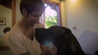 An owner petting, kissing, and loving on his huge dog after she was bathed in slow motion