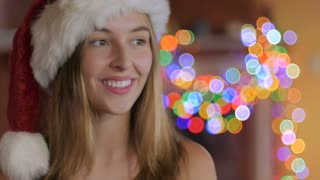 An pretty young woman winking, laughing and wearing a Santa hat in front of colored Christmas lights during the holiday season.