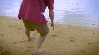 Attractive man in casual red shirt draws a heart in the sand with a stick on a beautiful tropical vacation beach.