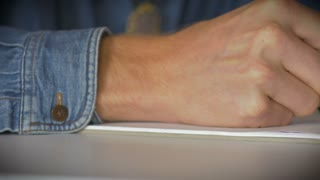 Close up dolly shot of a mans hand holding a pen writing and drawing on white paper in a notebook.