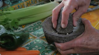 Close up hand held puch-in and push-out of a senior man grinding black and white pepper with a mortar and pestle by hand next to fresh vegetables