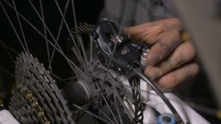 Close up of a bike mechanic's hands making minor adjustments to the disc brakes of a mountain bike on a garage or repair shop.