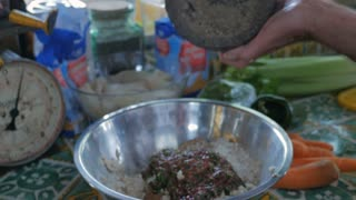 Close up of a cook adding ground pepper from a mortar and pestle to matzo ball mix for soup.