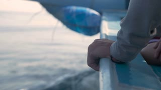 Close up of a hand holding the side of a boat as it speeds through water on an ocean, lake, or river.
